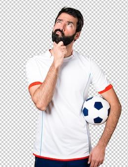 Fußballspieler, der ein fußballkugeldenken hält
