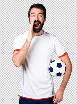 Fußballspieler, der ein fußballkugelschreien hält