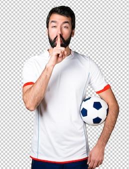 Fußballspieler, der einen fußball hält, der ruhegeste macht