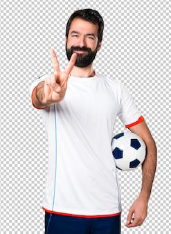 Fußballspieler, der einen fußball macht sieggeste hält