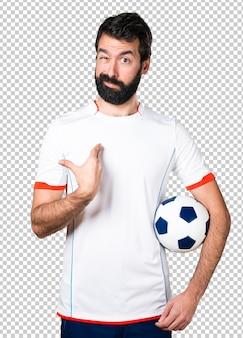 Fußballspieler, der einen fußball macht überraschungsgeste hält