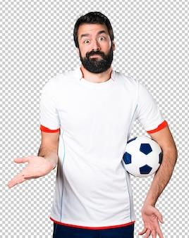 Fußballspieler, der einen fußball macht unbedeutende geste hält