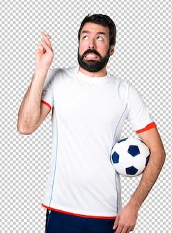 Fußballspieler, der einen fußball mit seiner fingerüberfahrt hält