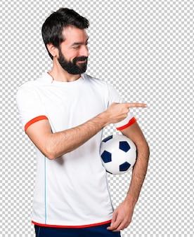 Fußballspieler, der einen fußball zeigt auf den seitenträger hält