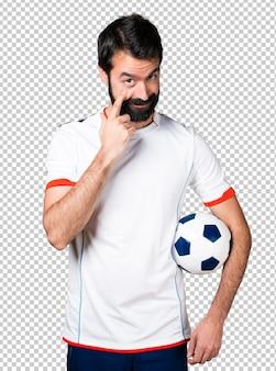 Fußballspieler, der einen fußball zeigt etwas hält