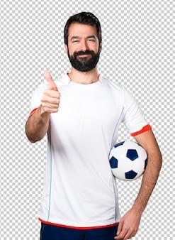 Fußballspieler, der oben einen fußball mit dem daumen hält