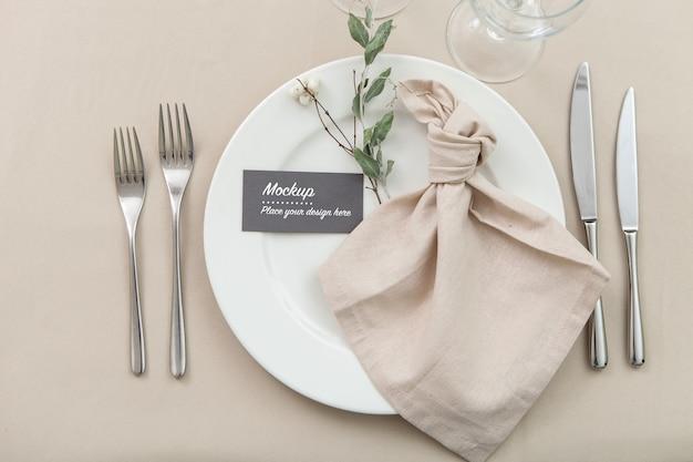 Gästekartenmodell auf gedecktem tisch mit serviette und grünem zweig verziert