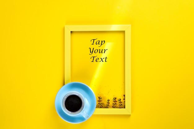 Gelber rahmen mit einem sonnenstrahl und einer tasse tee auf ihm, draufsicht über ein gelbes papier