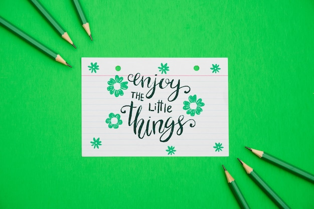 Genießen sie das kleine zitat auf blumenweißbuch und grünem hintergrund