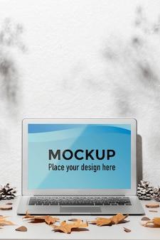 Geöffnetes laptop-modell auf dem tisch, umgeben von herbstlaub