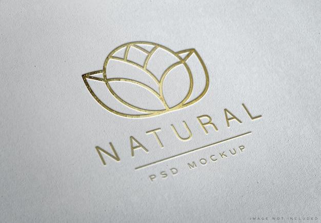 Geprägtes goldenes logo auf weißer papierstruktur
