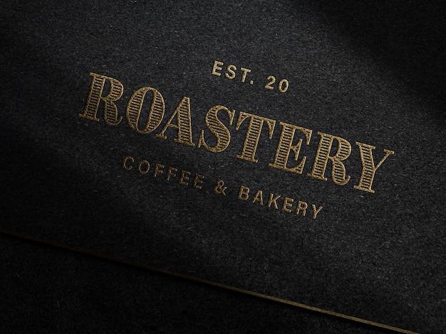 Geprägtes goldenes logo-modell auf dunklem papier