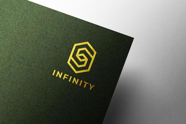 Geprägtes goldenes logo-modell auf grünem kraftpapier