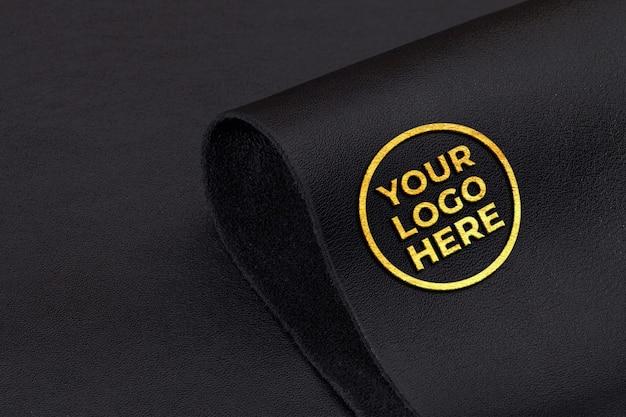 Geprägtes goldenes logomodell auf schwarzem lederhintergrund