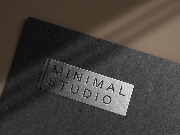 Geprägtes silbernes logo-modell auf dunklem papier