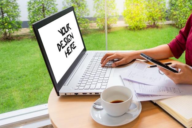 Geschäftsfrau, die auf laptop mit leerem weißem bildschirm schreibt