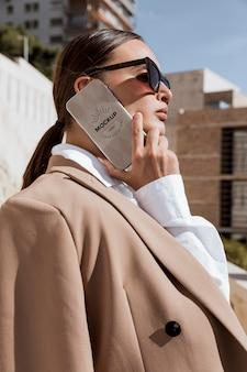 Geschäftsfrau, die mit dem telefonmodell spricht