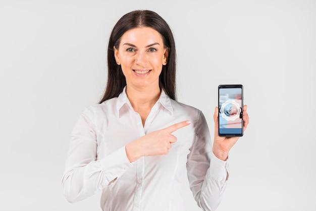 Geschäftsfrau, die smartphonemodell für werktag hält