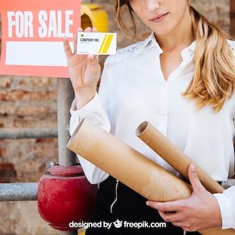 Geschäftsfrau, die visitenkarte vor baustelle zeigt