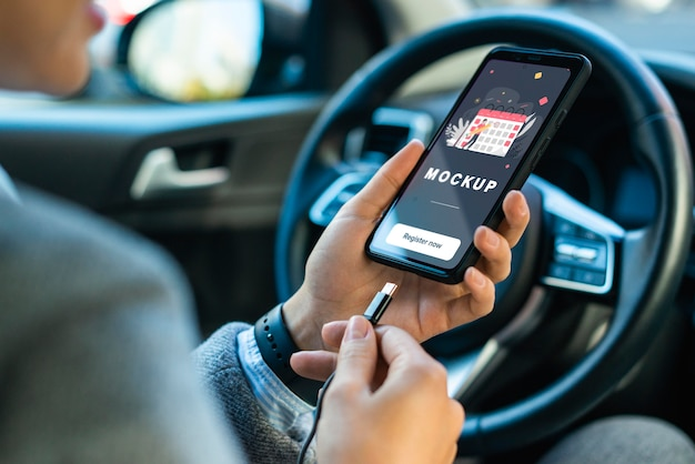 Geschäftsfrau im auto, das telefonmodell hält