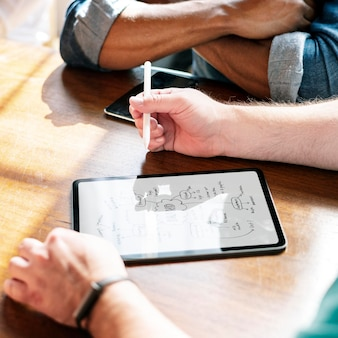 Geschäftsleute, die ein projekt auf einem digitalen tablet-mockup planen