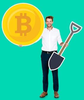 Geschäftsmann, der bitcoin-kryptowährung hält und konzeptikonen gewinnt