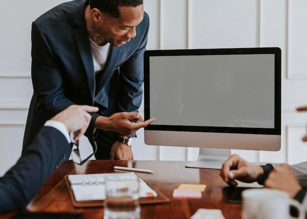 Geschäftsmann, der ein projekt auf einem computer-desktop-modell präsentiert
