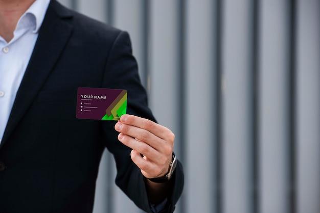 Geschäftsmann, der firmenvisitenkarte hält