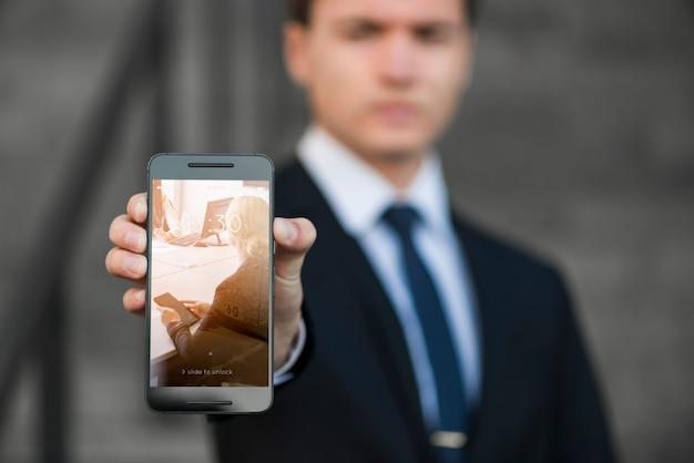 Geschäftsmann, der smartphonemodell darstellt
