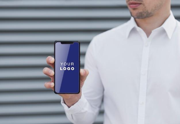 Geschäftsmann, der smartphonemodell hält