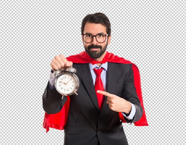 Geschäftsmann gekleidet wie der superheld, der eine uhr hält