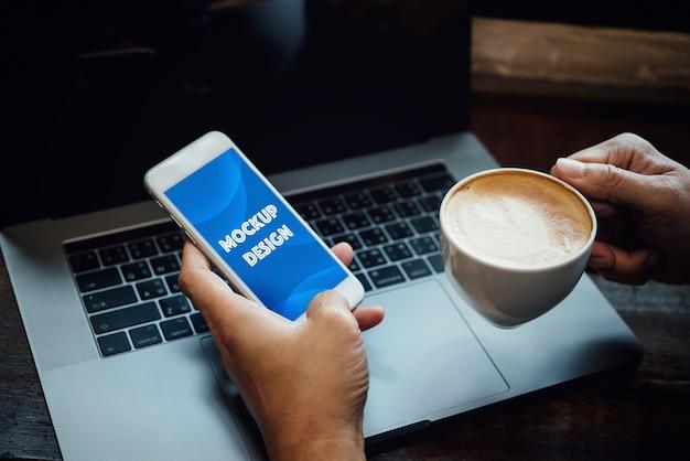 Geschäftsmannhand unter verwendung des laptops und handy, die online an der kaffeestube im morgenlicht arbeiten.