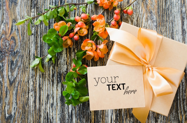 Geschenkbox mit schleifenband, leerem etikett und zartem blühendem zweig.
