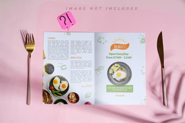 Geschirrset serviert gabel und messer mit broschüre.