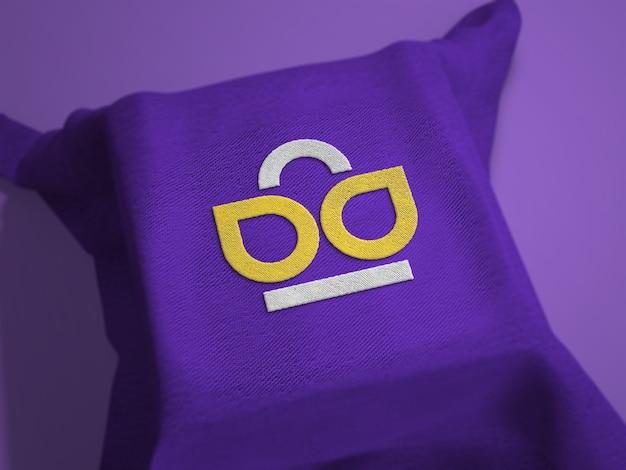 Gesticktes logo-modell auf stoff über quadratischer oberfläche