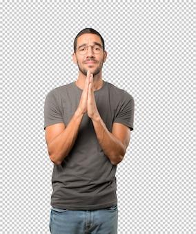Glückliche betende geste des jungen mannes