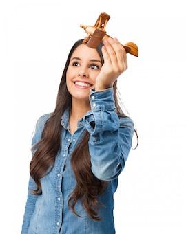 Glückliche frau mit ihrem holz-flugzeug spielen