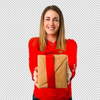 Glückliche junge blonde frau, die ein geschenk anhält