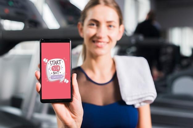 Glückliche sportliche frau, die smartphonemodell darstellt