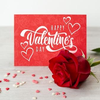Glückliche valentinstagbeschriftung auf roter karte mit rotrose