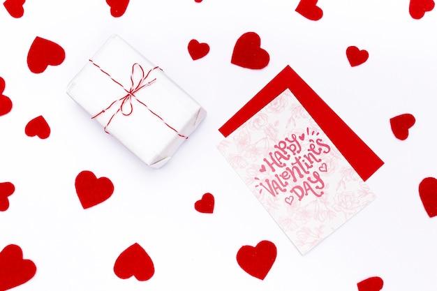 Glückliche valentinstagkarte nahe bei eingewickeltem geschenk