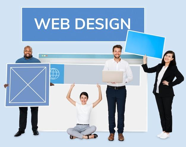 Glückliche verschiedene leute, die ein webdesignbrett halten