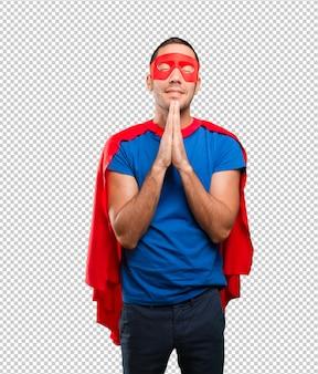 Glücklicher betender superheld