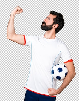 Glücklicher fußballspieler, der einen fußball hält
