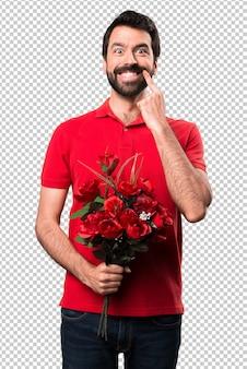 Glücklicher gutaussehender mann, der blumen hält