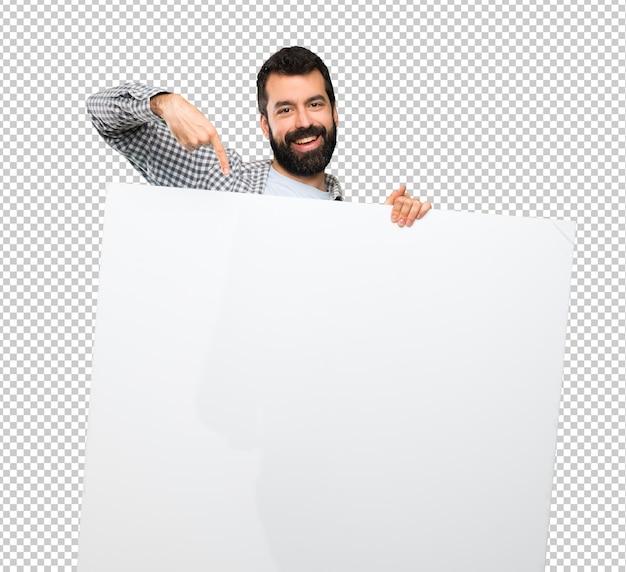 Glücklicher gutaussehender mann mit dem bart, der ein leeres plakat hält