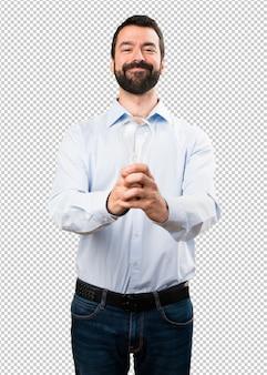 Glücklicher gutaussehender mann mit dem bart, der eine birne hält