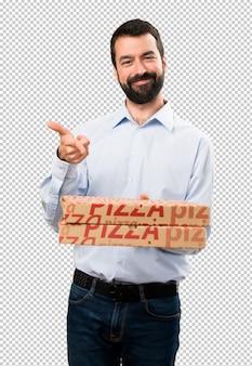 Glücklicher gutaussehender mann mit dem bart, der pizzas hält