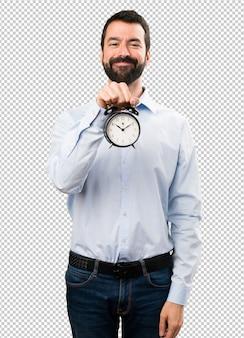 Glücklicher gutaussehender mann mit dem bart, der weinleseuhr hält