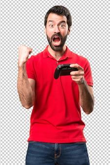 Glücklicher hübscher junger mann, der videospiele spielt